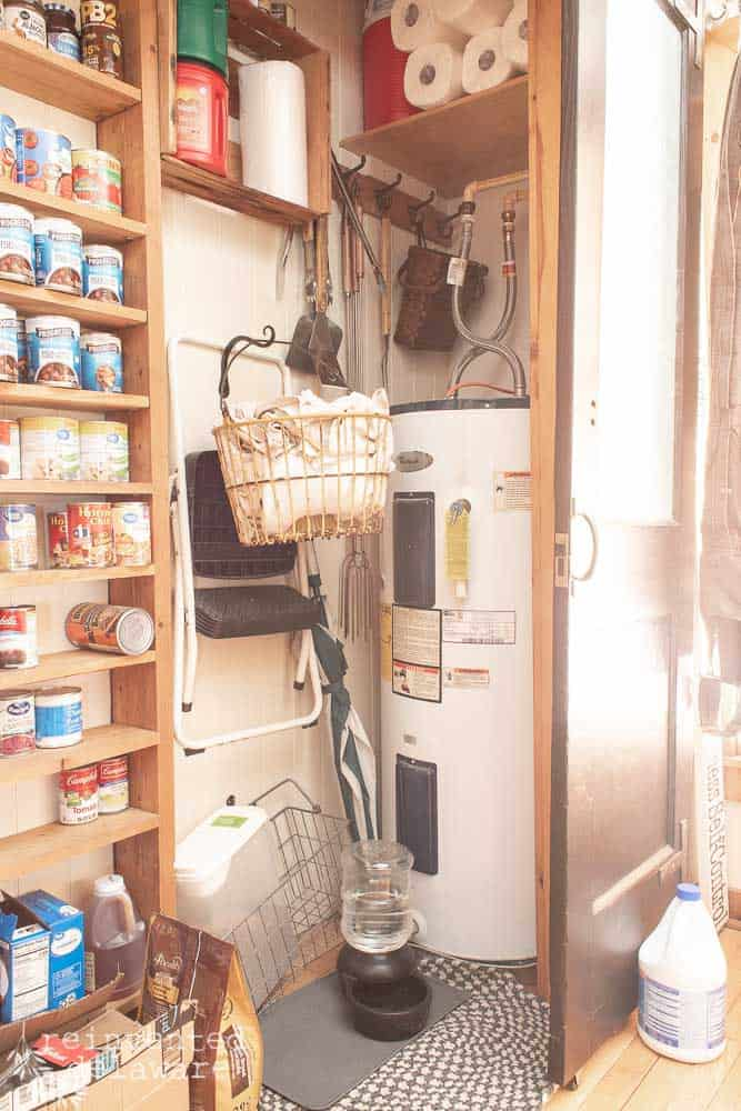 messy area in pantry closet with laundry items and hot water heater