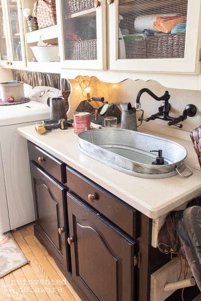 china cabinet converted to laundry room cabinet with galvanized tub sink