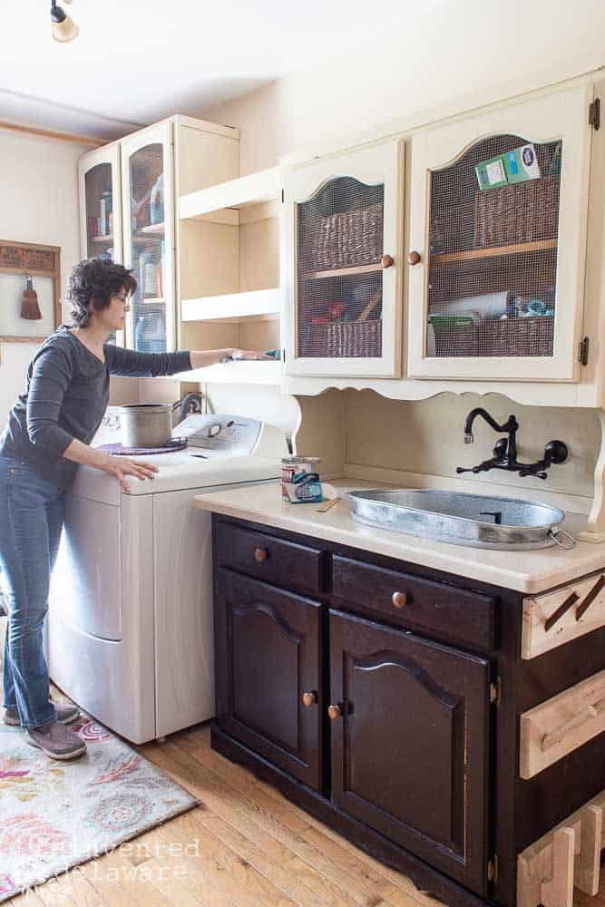 lady cleaning shelving and cabinets before painting
