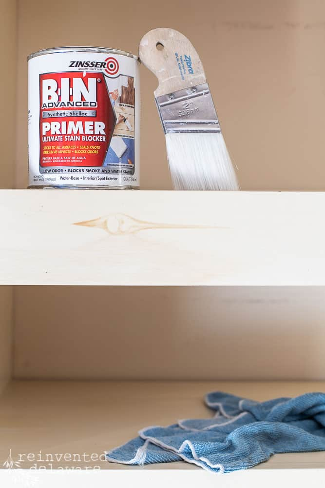 bleeding knot coming through painter surface on shelf with can of Zinsser Primer and Zibra paint brush