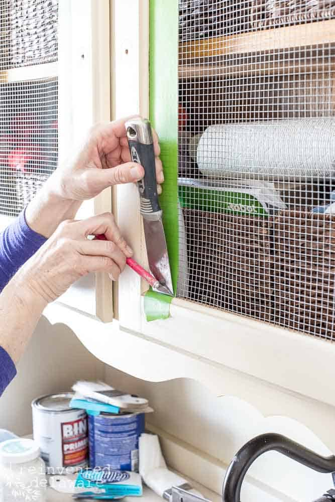 close up of lady using frog tape to prep cabinet for painting