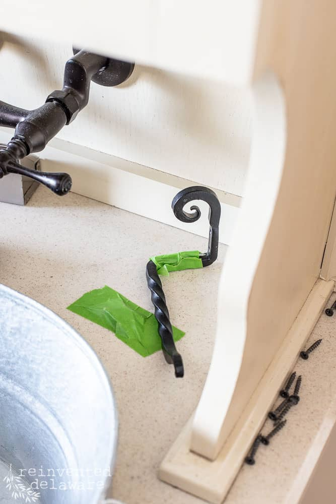 close up showing how to use frog tape to save lost cabinet door screws from getting lost