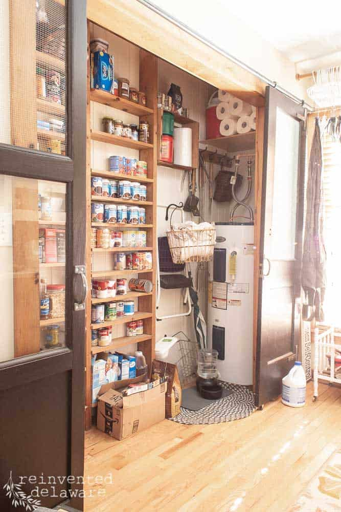 messy pantry closet in laundry room with hot water heater exposed