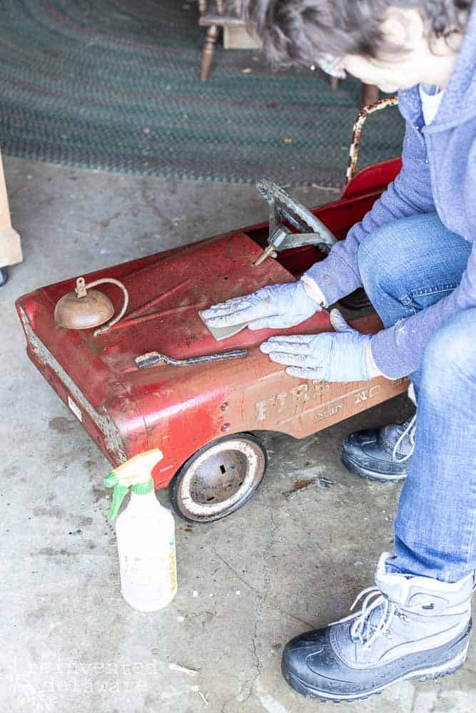 lady demonstrating how to clean rust off antique metal toy fire truck with vinegar and scrubbing