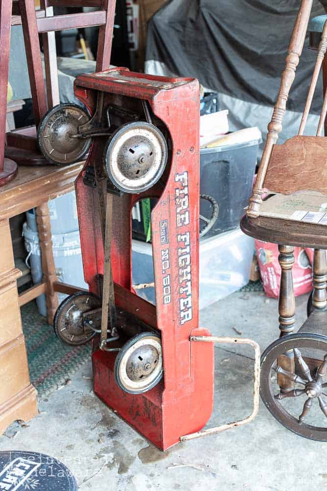 antique metal fire truck sitting on end so moisture can drip off