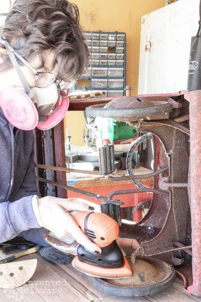 lady using mouse sander to clean rust off antique metal toy fire truck