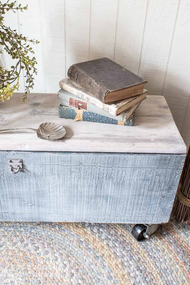 close up of old wooden toolbox with casters, book and plant on top