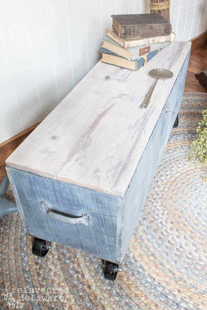 old wooden toolbox with casters and book on top showing white waxed lid