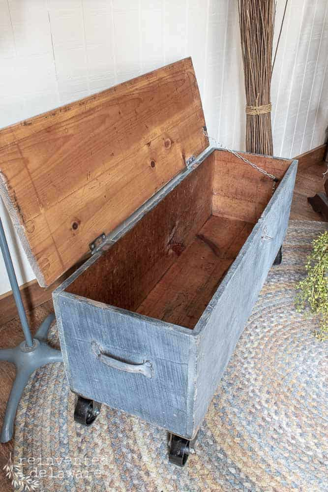 inside of old wooden toolbox showing chain on lid
