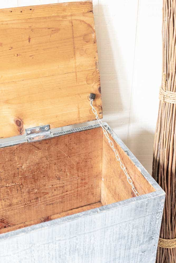 inside of old wooden toolbox showing chain that holds lid from falling open