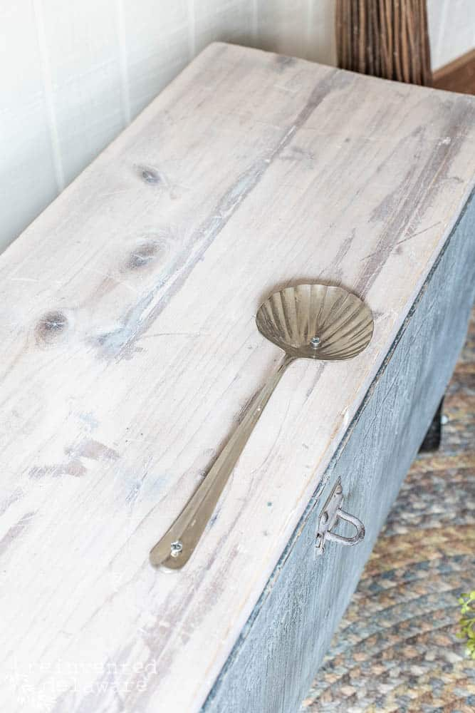 repurposed wooden toolbox lid with silver spoon handle