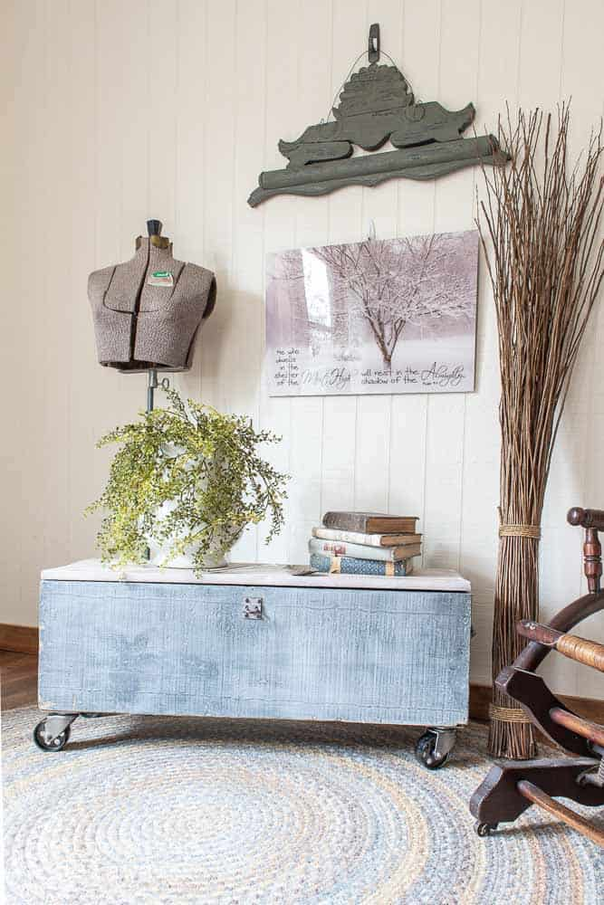 old wooden toolbox with casters, book and plant on top next to a rocking chair with wall art