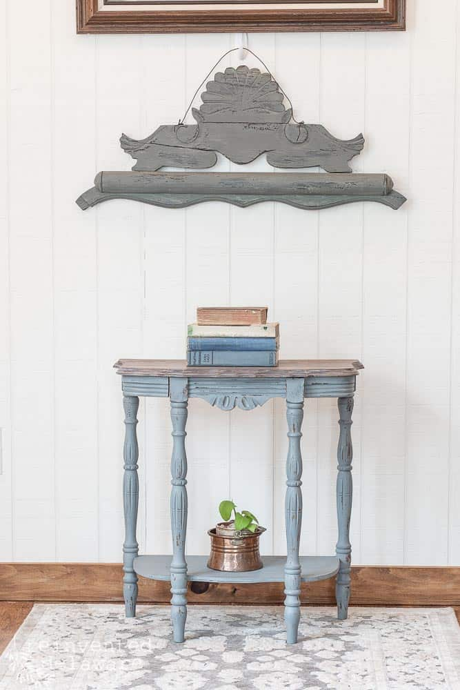Demilune table with stack of books on top and wall decor
