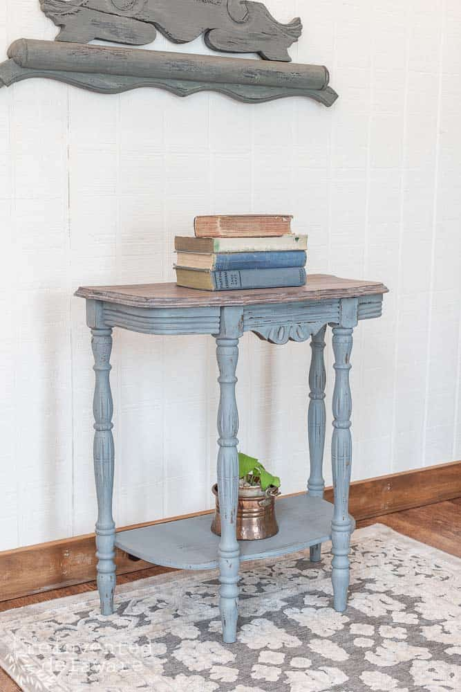 side view of Demilune Table makeover with stack of book and plant