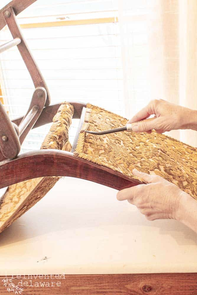 lady removing old decorative tacks on upholstered folding rocking chair