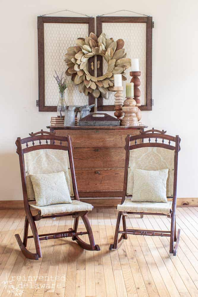 pair of folding Eastlake Rockering chairs with new upholstery and antique dresser and decor in background