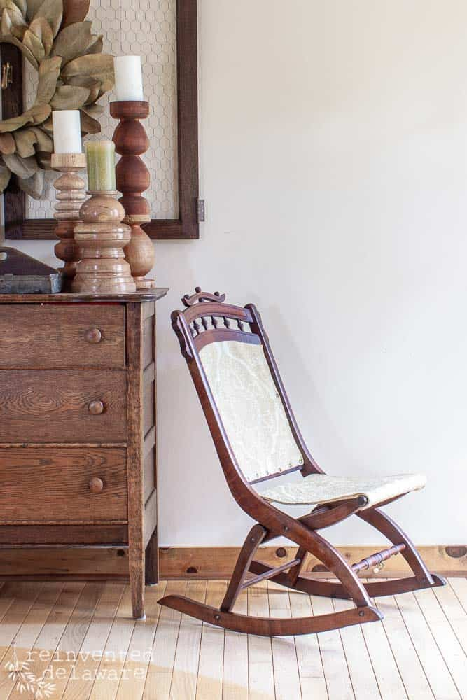 side view of rocking chair upholstery antique rocker sitting next to antique dresser with decor
