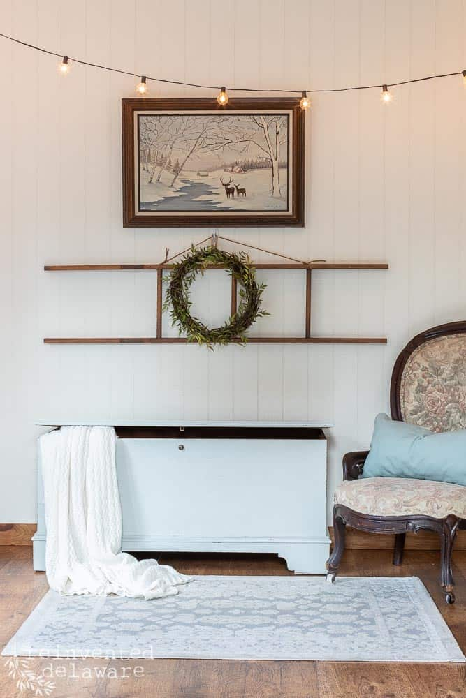 staged shot of painted blanket and hope chest including wall decor and vintage chair