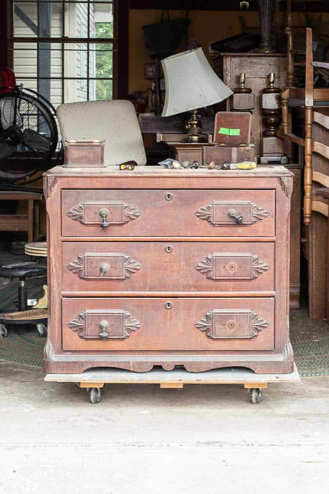 antique gentlemen's dresser before makeover sitting in workshop
