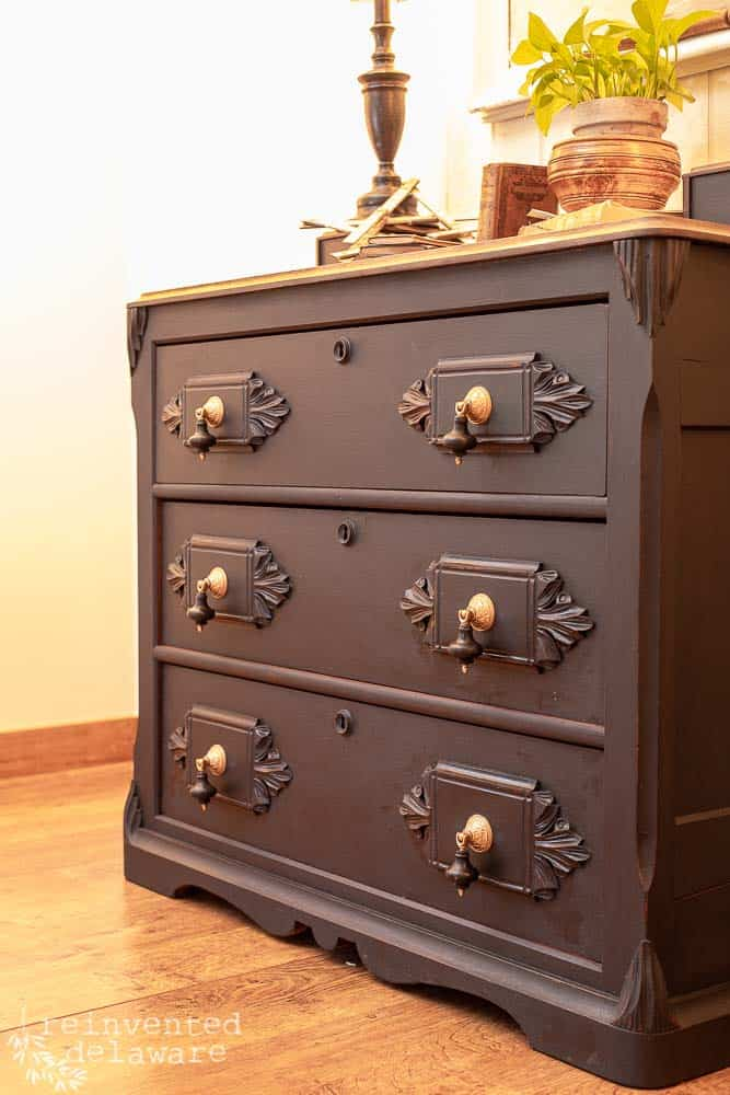 side angle view of front of antique gentlemen's dresser showing carved details