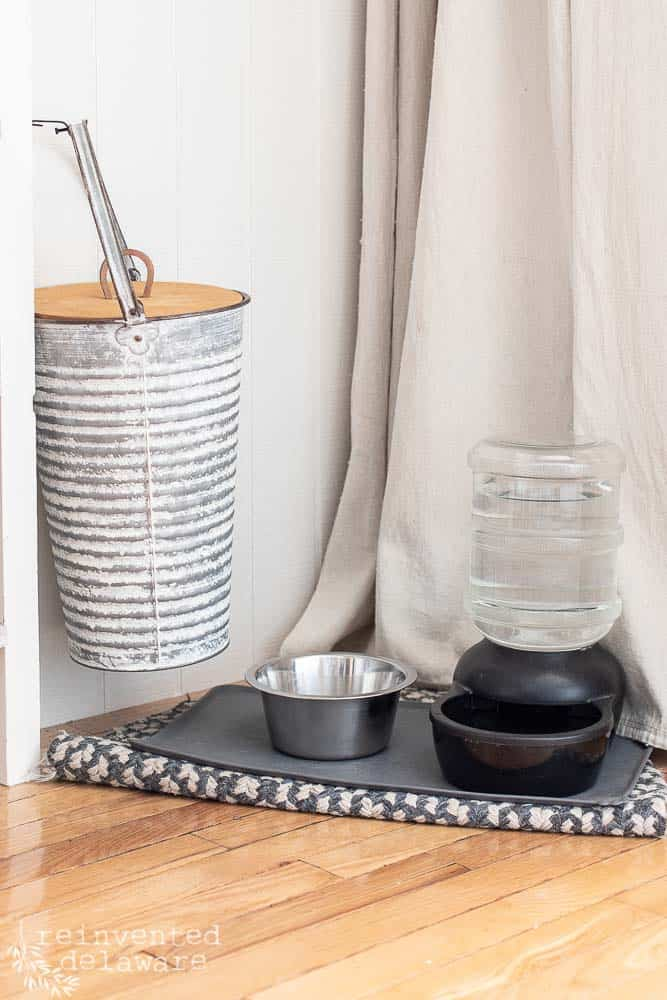 close up shot of doggie food and water bowl and vintage style food container in laundry room