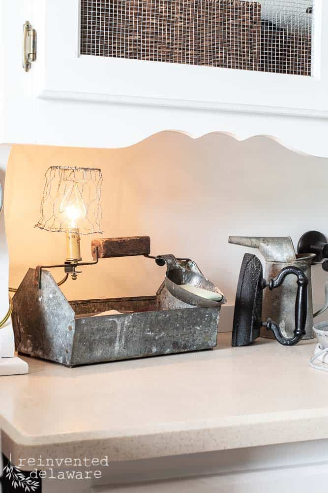 metal tool caddy used as scrub brush and soap holder in laundry room with clip lamp attached on side