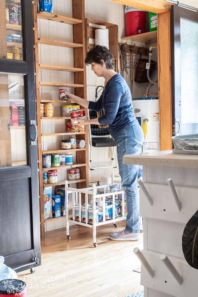 lady removing pantry items from pantry shelves