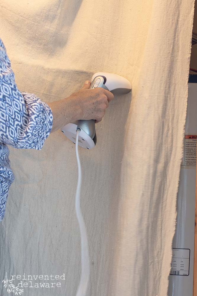 lady using steamer on dropcloth curtain/close up shot