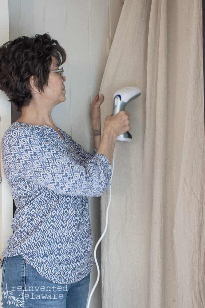 lady using steamer on dropcloth curtain
