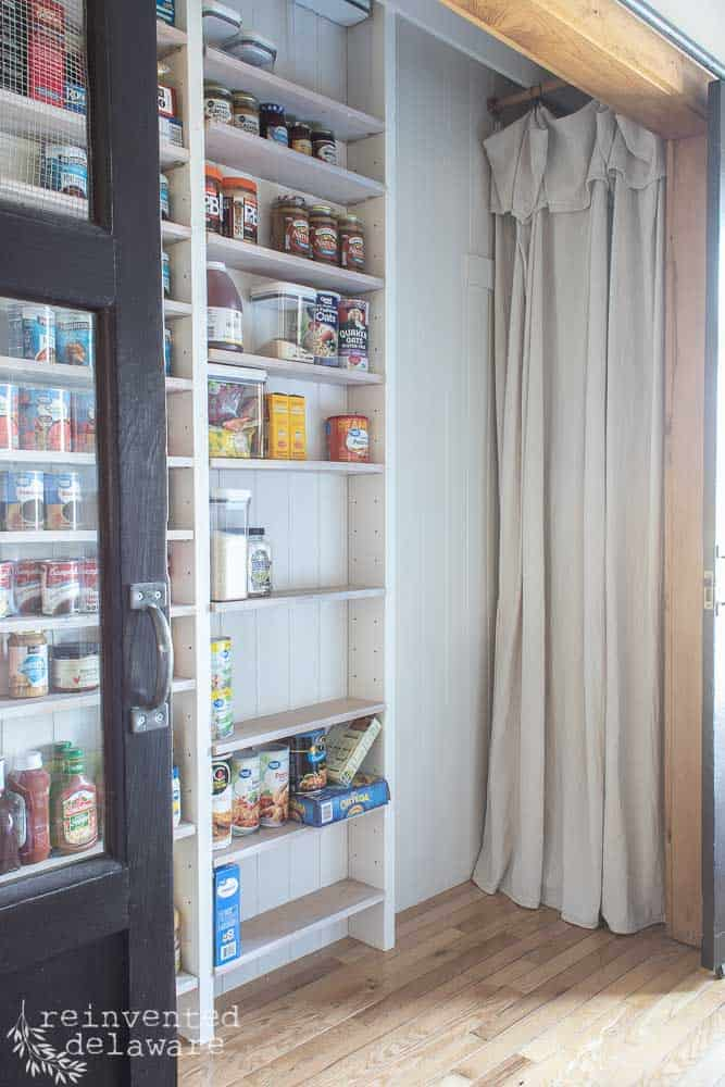 view of pantry with narrow shelves and canned goods on shelves and dropcloth curtain hiding water heater