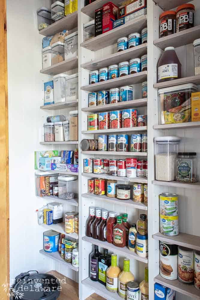 view of pantry with narrow shelves and canned goods on shelves