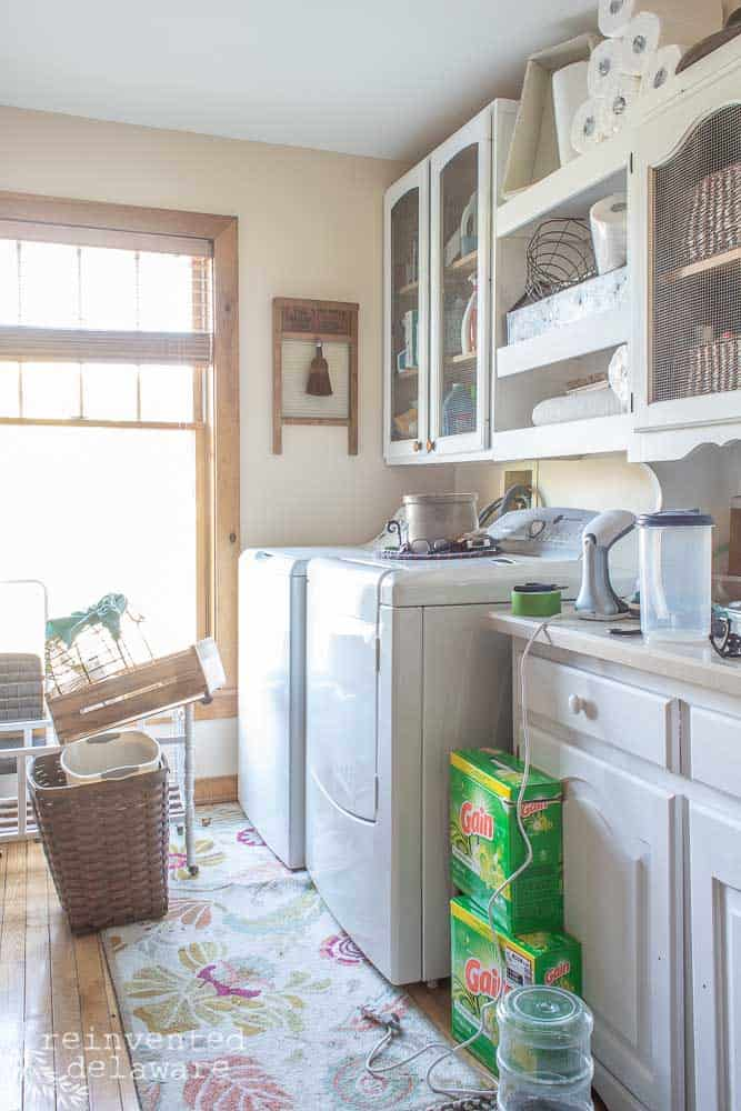 laundry room with washer, dryer and other items with laundry soap and steamer on counter