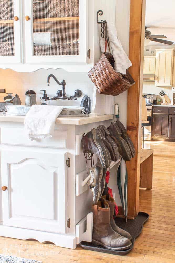 side view of laundry room cabinet with shoe pegs, basket for scarves and gloves and towel holder
