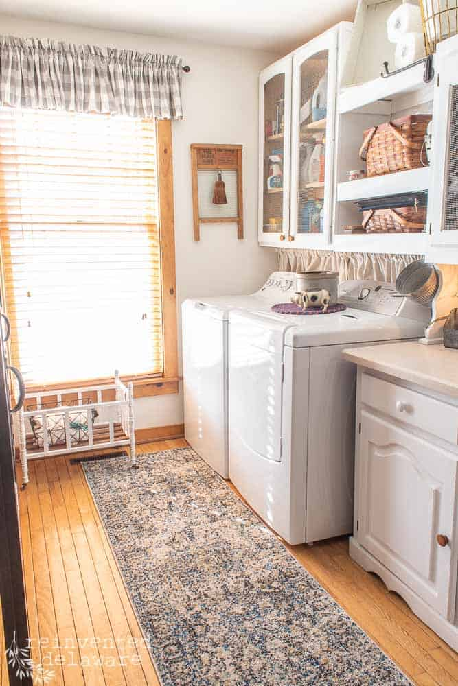 full view of laundry room that has been made over to be functional. washer, dryer, storage cabinet, shelving with baskets, new rug
