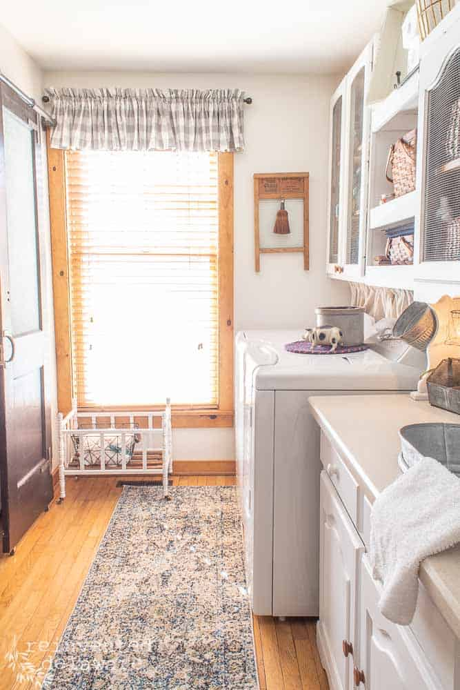 full view of a functional laundry room showing washer, dryer, storage cabinet, new checked curtain, small crib for laundry basket