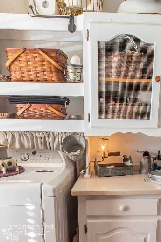 side view of laundry room washer dryer storage cabinet with baskets and decorative items