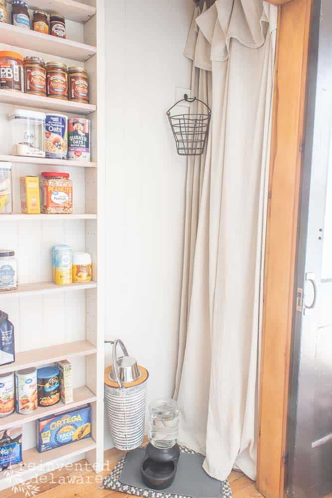 drop cloth curtain hiding a hot water heater in a functional laundry room
