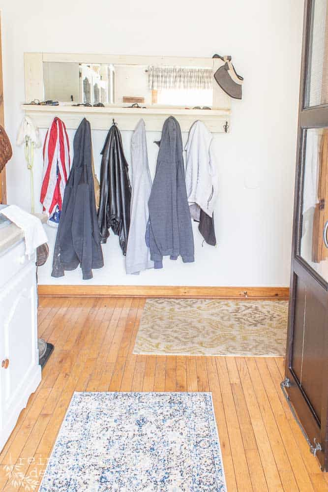 jackets hanging on a vintage coat rack with mirror in a functional laundry room