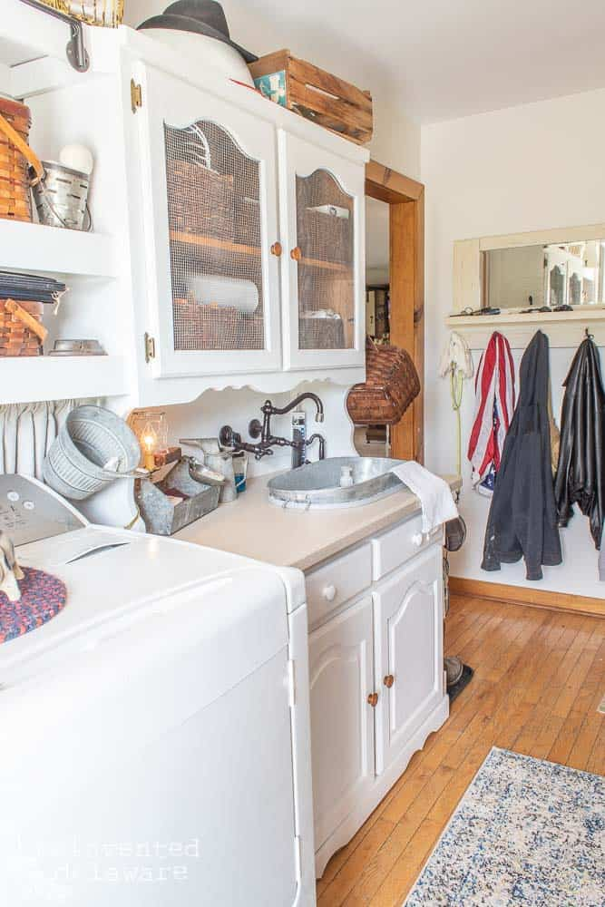 side view of laundry room cabinets with baskets and above cabinet storage