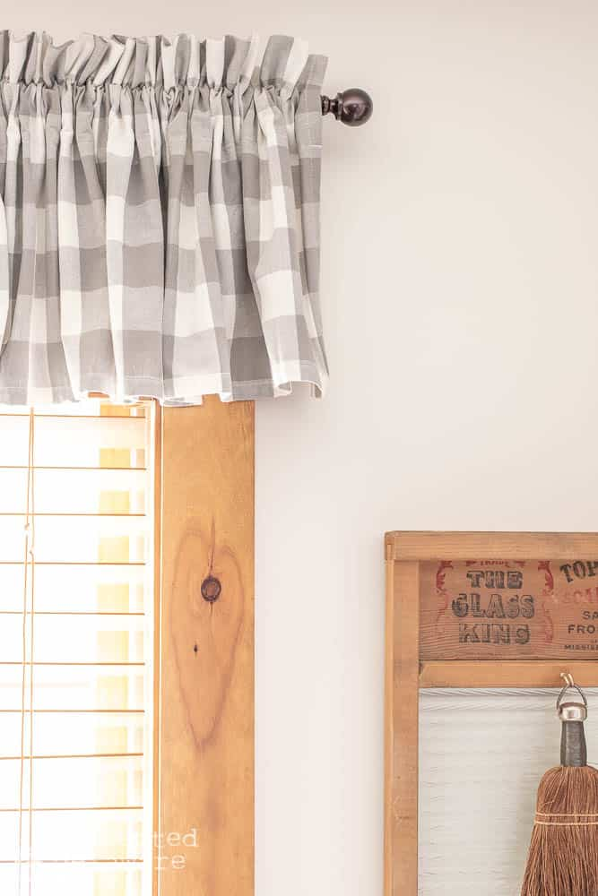 close up shot of laundry room window valance in gray and white check also showing vintage style washboard and wish broom