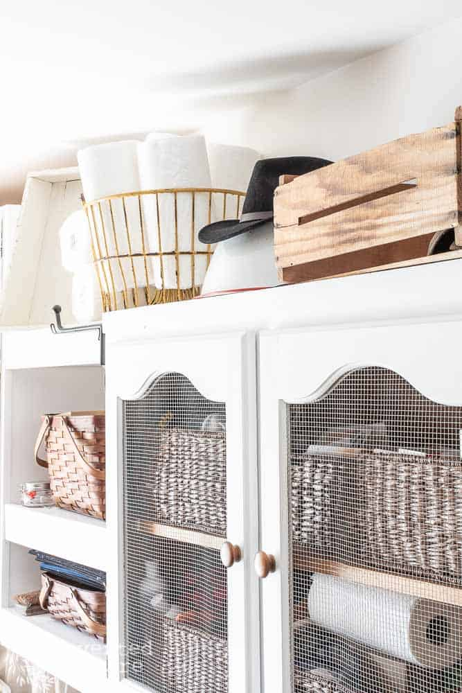 top of laundry room shelves for storage of large hat and paper towels
