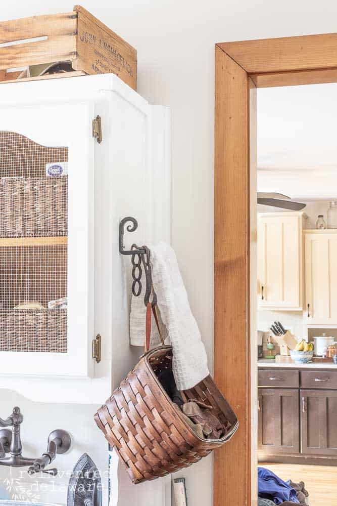 side of cabinet in laundry room with towel hook and basket for gloves and hats