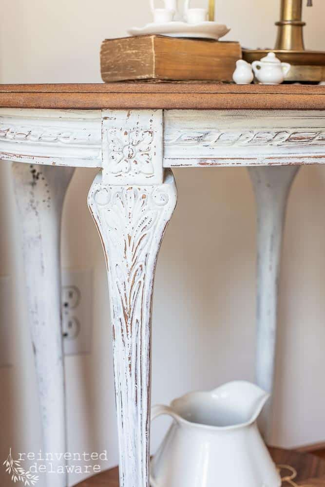 close up of painted carved areas on vintage wood inlay side table