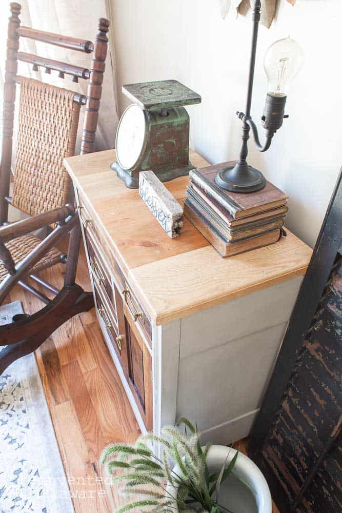 close up of farmhouse style wood top on restored antique washstand staged with vintage items like books and lamp