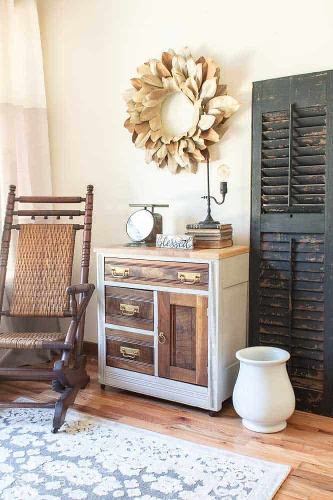 after shot of antique washstand makeover project staged with antique rocker, shutter and magnolia wreath