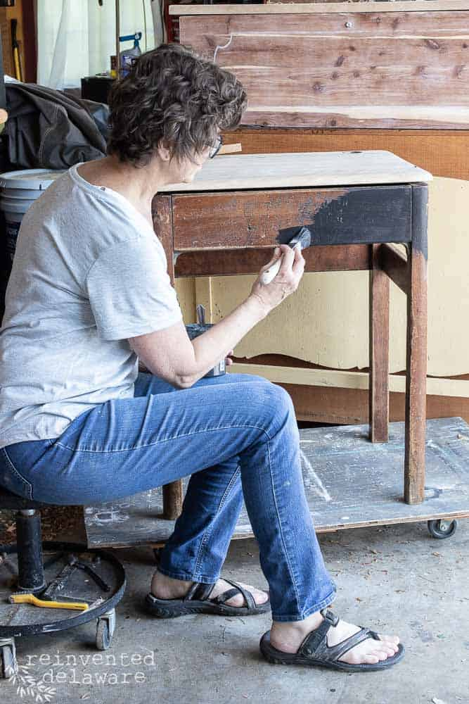 lady painting first coat of Miss Mustard Seed Milk paint in Typewriter black on antique school desk