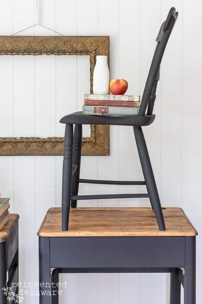 side view of refurbished antque chair with stack of books and an apple sitting on top of antique desk