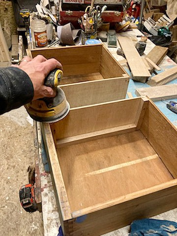 man showing sander on top of drawer with new sides or repurposed dresser bathroom vanity makeover