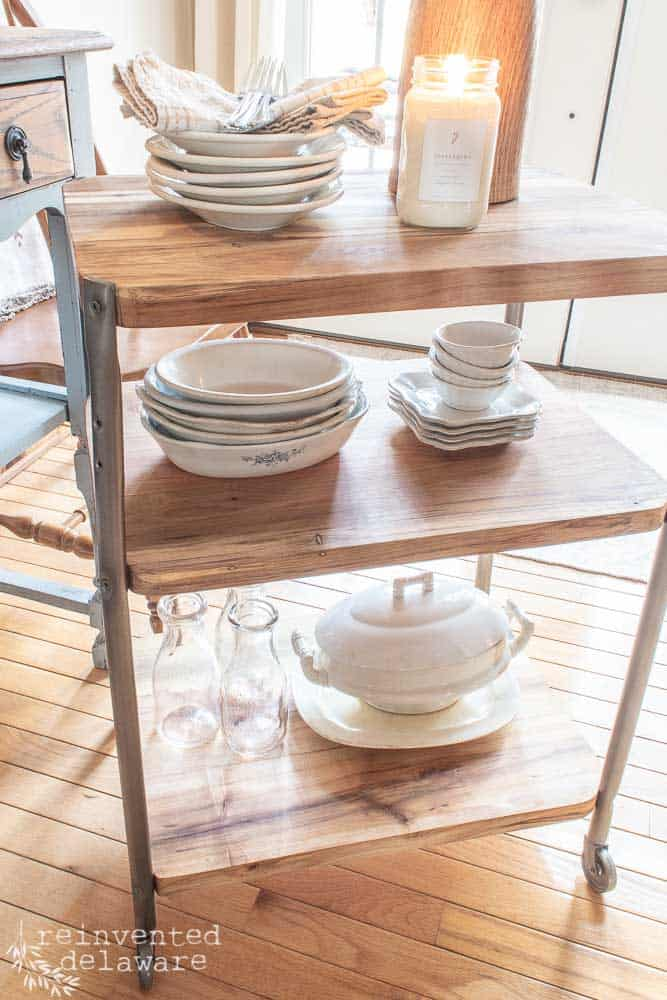 downward view of repurposed school cart staged with ironstone dishes and candle