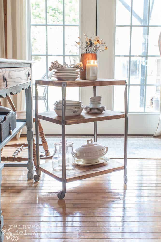 full view of upcycled metal school cart showing reclaimed lumber wood shelves staged with ironstone dishes, candle and silverware